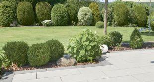 Eine Terrasse mit Blick ins Grüne. Die Rasenfläche wird abgegrenzt von einem k...